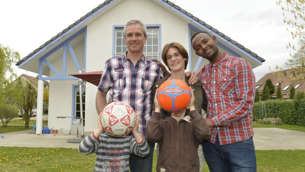 Ein Mann, eine Frau und zwei Kinder mit einem Flüchtling.