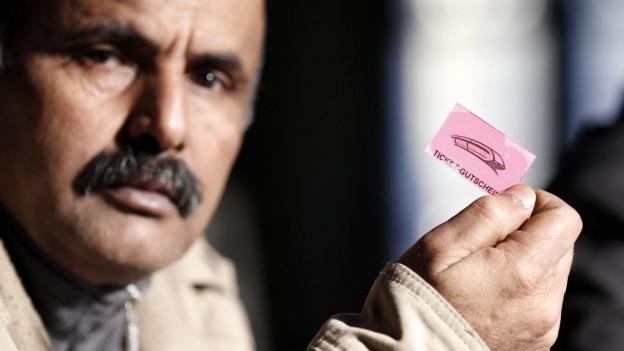Ein dunkelhäutiger Mann mit Schnurrbart hält einen rosa Gutschein in der Hand.