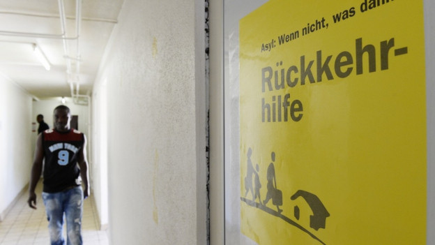 Blick in den Gang einer Asylunterkunft, ein junger Schwarzer kommt uns entgegen, an der Wand ein Plakat, das auf Rückkehrhilfe aufmerksam macht.