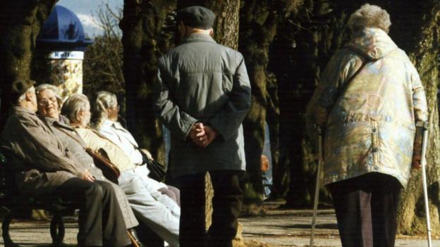 Ein altes Ehepaar von hinten spaziert in der Sonne.