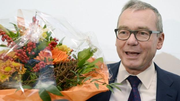 Ein Mann mit Brille und Anzug hält einen Blumenstrauss.