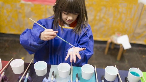 Ein Mädchen im Kindergarten mischt blauen Farben.