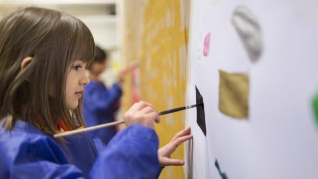 Eine Kindergärtnerin malt ein Bild auf eine Tafel.