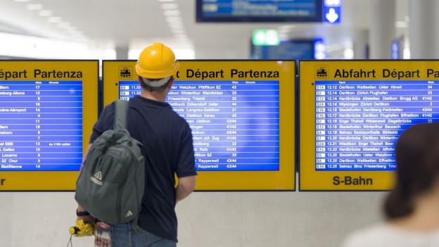 Ein Mann steht vor einem Bildschirm mit Fahrplan-Informationen.