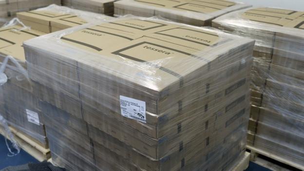 Pakete mit Unterkunfts-Modulen liegen auf Palletten in einer Messehalle in Zürich