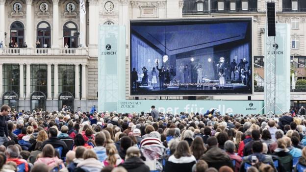 Zuschauermenge verfolgt die Liveübertragung einer Oper