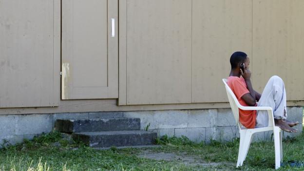 Ein Flüchtling sitzt in einem weissen Plastikstuhl.