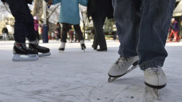 Blick auf die Beine von schlittschuhlaufenden Menschen