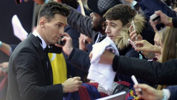 Lionel Messi verteilt auf dem roten Teppich Autogramme an die Fans