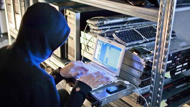 Ein Hacker tippt Daten in einen Rechner ein (Symbolbild)