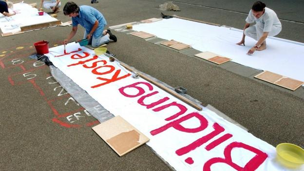Eine Frau kniet auf dem Boden und bemalt ein Plakat.