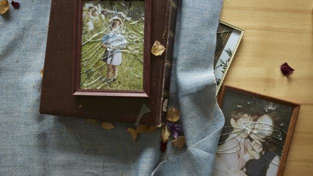 Symbolbild: Auf einem Tisch liegen Bilderrahmen mit zerbrochenen Scheibe, ein Fotoalbum und vertrocknetes Laub und Blütenblätter.