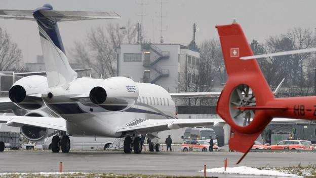 Ein parkiertes Flugzeug, davor der rote Heckrotor eines Helikopters