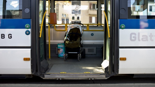 Ein Bus, der an Haltestelle wartet mit offener Türe.