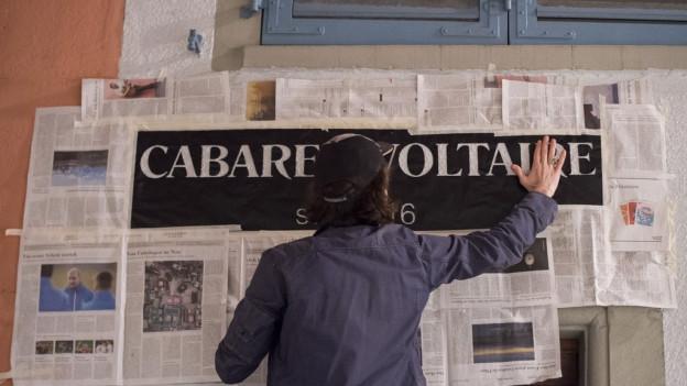 Ein Mann vor vielen Zeitungen an einer Wand.