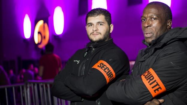 Zwei Sicherheitsmänner mit orangen Armbinden sthen mit verschränkten Armen an einer Abschrankung