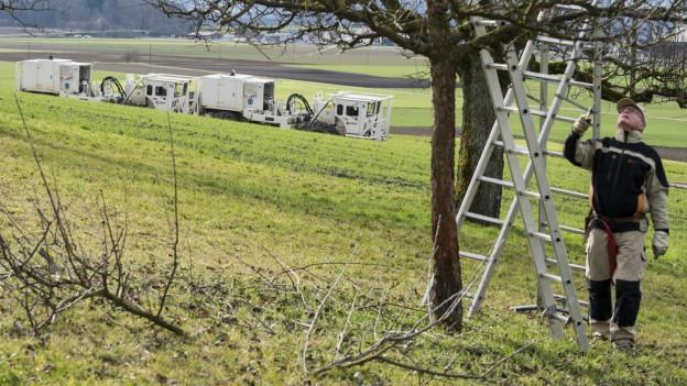 Ein Bauer steht unter einem Baum, dahinter weisse Fahrzeuge der NAGRA