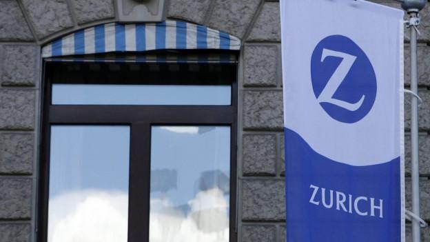 Ein Fenster der Zurich Versicherung, in dem sich ein blauer Himmel spiegelt