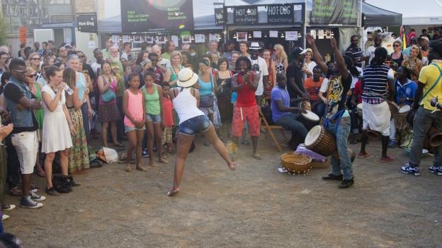 Ein Mann aus Afrika tanzt, umringt und angefeuert von Publikum
