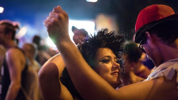Eine junge Frau und ein junger Mann tanzen an einer Party