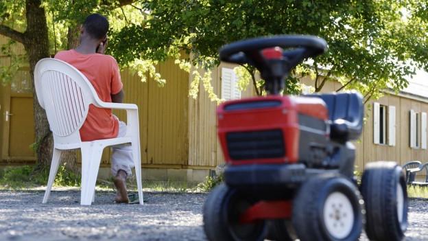 Ein Flüchtling sitzt auf einen Plastikstuhl im Asylzentrum Juch und telefoniert. Im Vordergrund ein Spielzeugtraktor