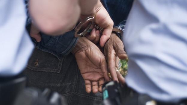 Polizisten legen einen Mann Handschellen an