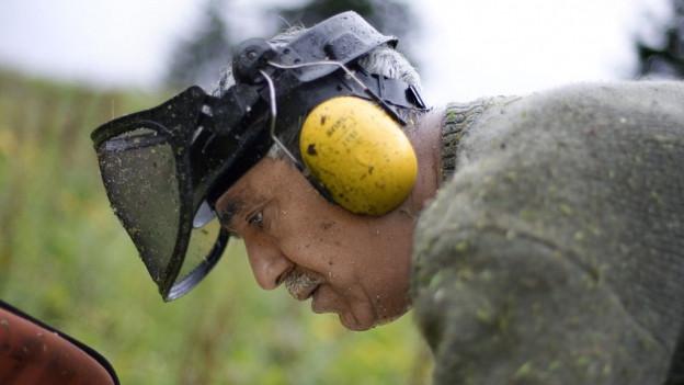 Ein Mann mit grauen Haaren und Schnurrbart trägt einen Lärmschutz.