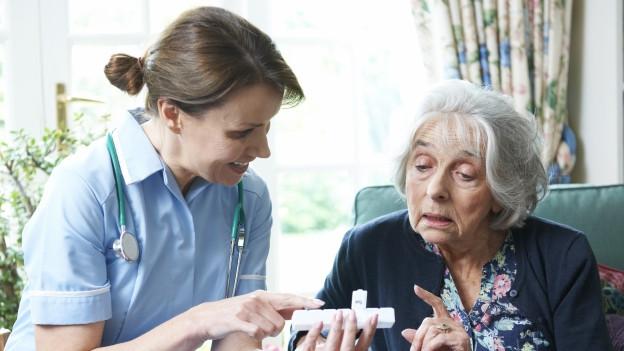 Eine Pflegefachfrau berät eine Seniorin
