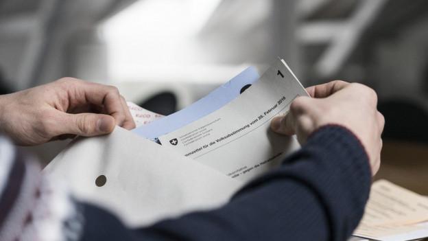Hände stecken Stimmzettel in ein Stimmcouvert