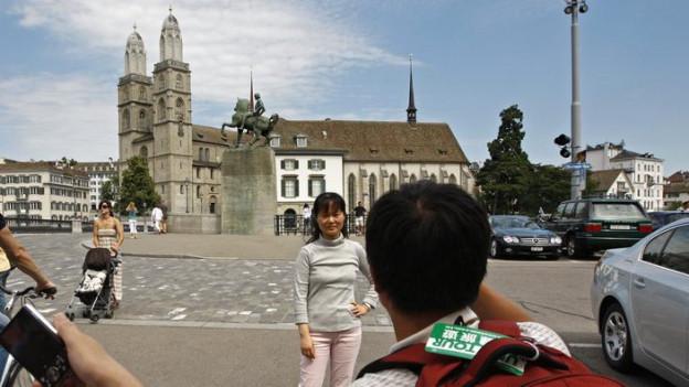 Touristen besuchen die Zürcher Altstadt, im Hintergrund das Grossmünster.