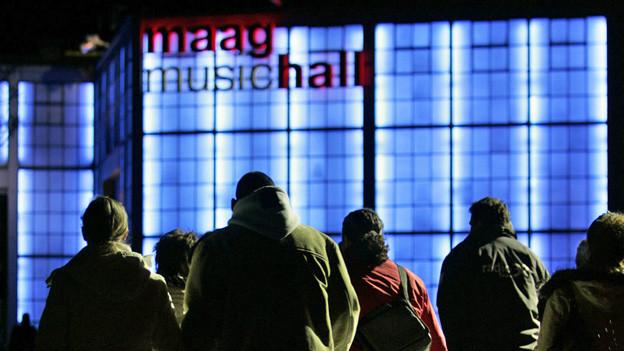 Die blau beleuchtete Maag-Halle bei Nacht.