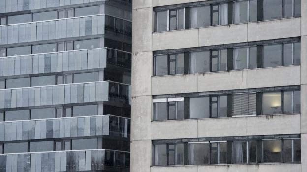 Nahaufnahme einer alten und neuen Hochhausfassade.