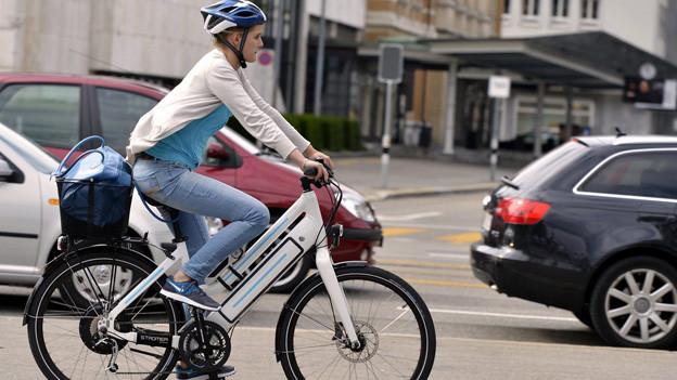 Eine Frau ist mit einem E-Bike auf einer Zürcher Strasse unterwegs.