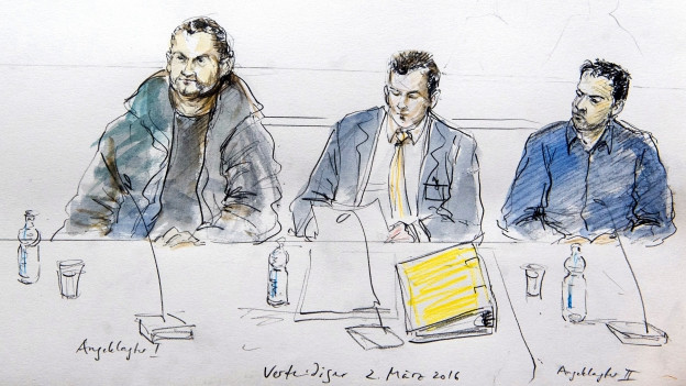 Eine Gerichtszeichnung von zwei der vier Angeklagten und ihrem Verteidiger.
