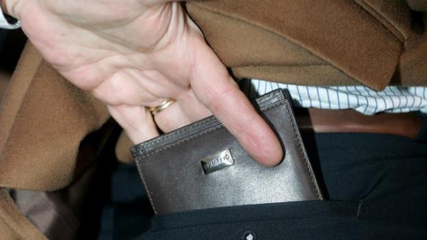 Ein Mann klaut ein Portemonnaie.