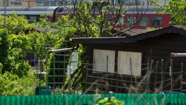 Ein Schrebergartenhaus mit vorbeifahrendem Zug im Hintergrund.