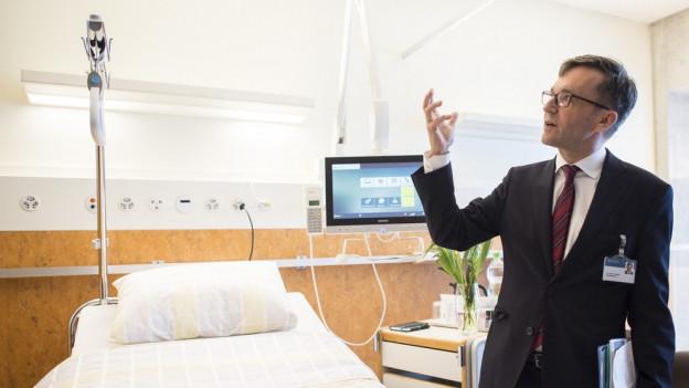 Ein Mann steht in einem Spitalzimmer.