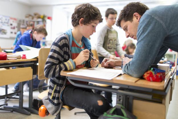 Ein Lehrer steht an einer Wandtafel vor einer Schulklasse