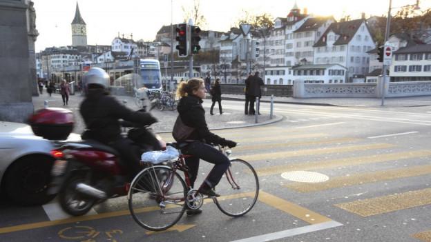 Eine Velofahrern zwischen Autos an einer Kreuzung.