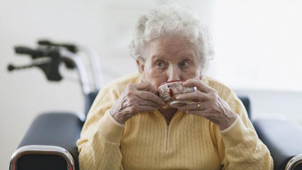 Eine ältere Dame trinkt Tee.