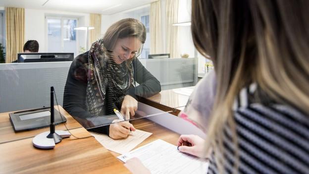 Eine Frau füllt an einem Schalter ein Formular aus.