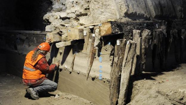 Ein Mann in Warnkleidung kniet neben einem archäologischen Fundstück.