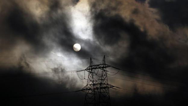 Strommast vor einem Vollmond und dunklen Wolken