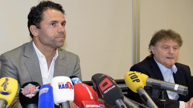 Uli Forte sitzt neben Präsident Anchillo Canepa
