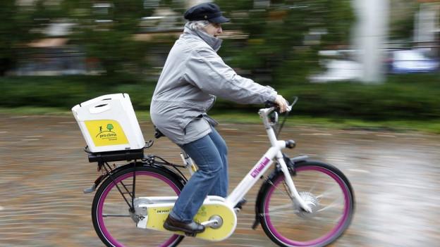 Eine ältere Frau fährt auf einem E-Bike.