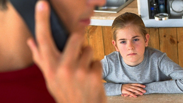 Ein Mädchen sitzt am Tisch und schaut mit bösem Blick auf einen Mann im Vordergrund, der telefoniert.