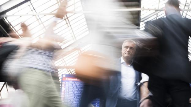 Pendler in der Querhalle des Züricher Hauptbahnhofs vor der grossen Anzeigetafel