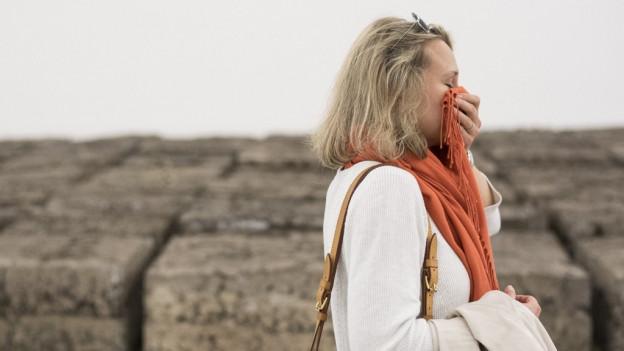 Eine Frau hält sich einen Schal ans Gesicht, dahinter Blöcke aus Klärschlamm.