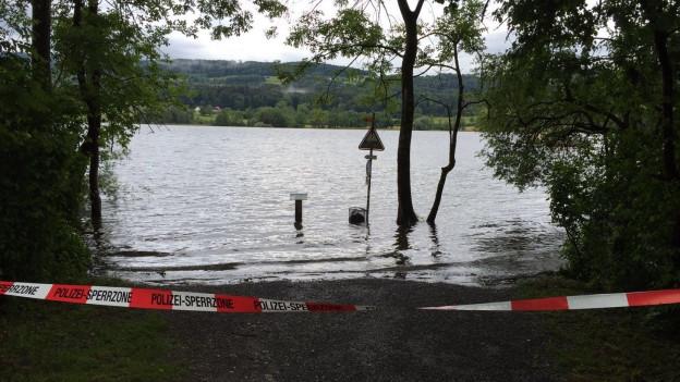 Seeufer mit Hochwasser und Absperrung