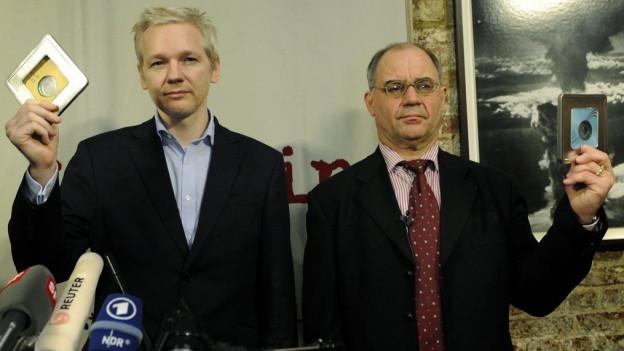 Zwei Männer mit je einer CD in der Hand, davor Radiomikrofone